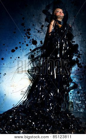 Young woman in black dress created from tape, smoke and spots. Dark dramatic colors.