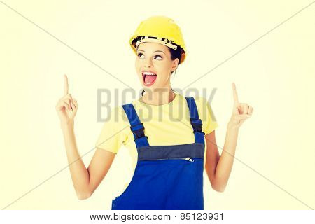 Happy female constructor pointing up.