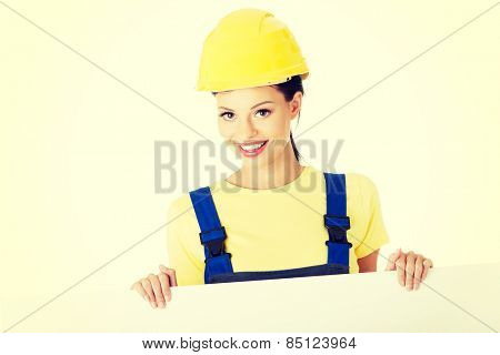 Happy female constructor holding empty banner.