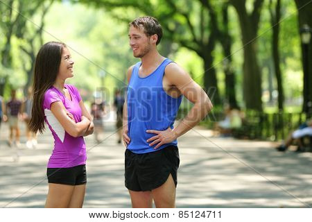 Happy runners couple talking after run in NYC park. Female and male adult athletes resting together in Central Park, New York city, wearing active tops and shorts sportswear for a summer workout.