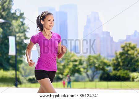 Run woman exercising in Central Park New York City with urban background of skyscrapers skyline. Active Asian female runner running with purple t-shirt and shorts sportswear.
