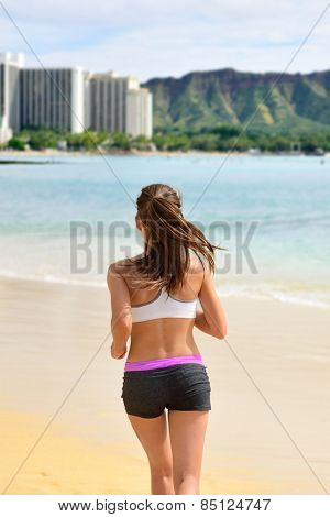 Active fit female sport runner jogging on beach. Woman jogger from behind working out her cardio by running on sunny Waikiki beach, Honolulu city, Oahu island, Hawaii, USA.