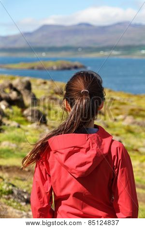Hiking woman in hardshell jacket in Iceland nature looking at view enjoying beautiful scenic landscape on hike. Healthy active lifestyle concept with woman looking away showing backside.