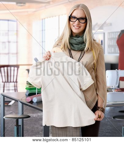 Portrait of happy casual trendy caucasian blonde fashion designer woman at studio. Smiling, standing, looking at camera.