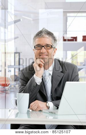 Happy mature businessman thinking at business office desk with laptop computer and coffee mug. Smiling, sitting, hand under chin, looking in the distance, wearing glasses.