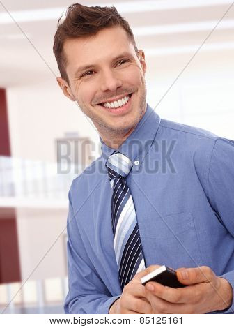 Cheerful young businessman with mobile phone at office center. Toothy smile, standing, tie, no jacket.