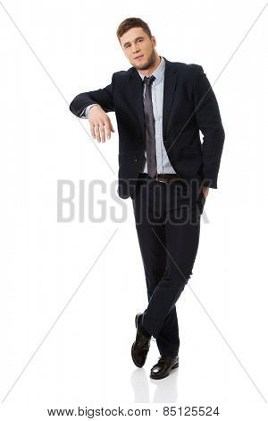 Handsome young businessman leaning on copy space.