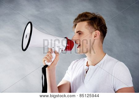 Young handsome man shouting in megaphone.