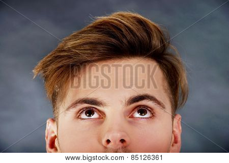 Handsome young man with brown eyes looking up.
