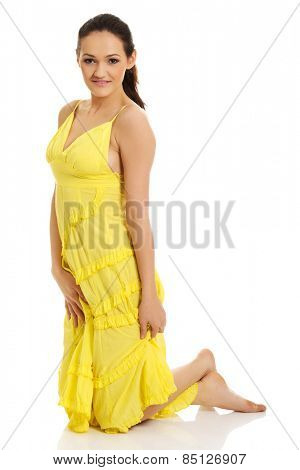 Beautiful woman sitting on knees in yellow summer dress.