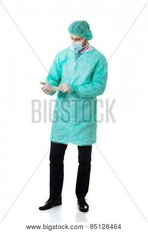 Handsome male surgeon putting on protective gloves.