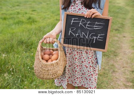 Woman holding basket of free range eggs on a sunny day