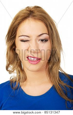 Beautiful happy woman blinks her eye.