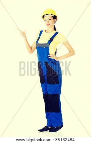 Happy beautiful female constructor pointing.
