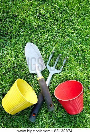 Gardening tools on green grass in the garden.