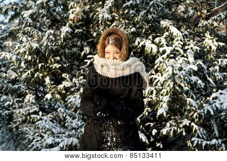 Happy teenage woman making snowball