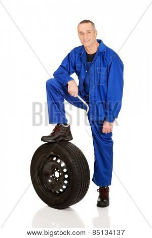 Mature car mechanic with a tire and wrench.
