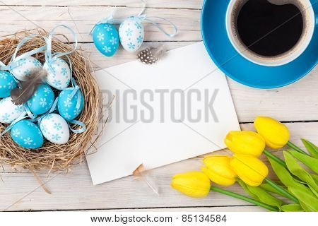 Easter background with blue and white eggs in nest, yellow tulips and greeting card over white wood. Top view with copy space