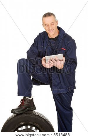Smiling mechanic with a tire and tablet.