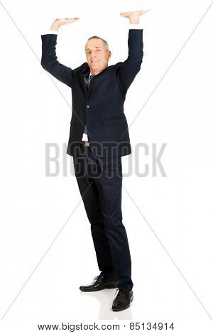 Full length businessman pushing invisible ceiling.