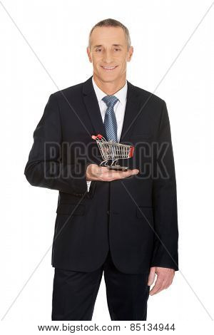Mature businessman holding small shopping cart.