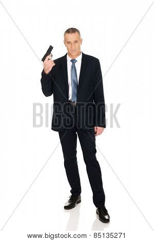 Mature serious mafia agent with handgun.
