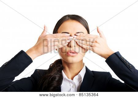 Portrait of young businesswoman covering eyes with hands.