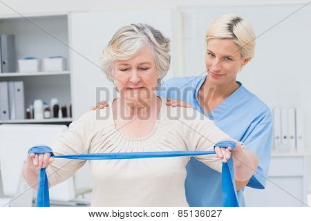 Portrait of confident nurse assisting senior woman in exercising with resistance band in clinic
