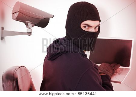 Hacker sitting and hacking laptop against cctv camera