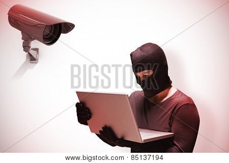 Hacker using laptop to steal identity against cctv camera