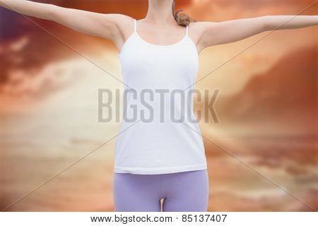 Woman standing with arms raised on countryside landscape against sunrise over magical sea