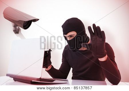 Focused burglar hacking into laptop against cctv camera