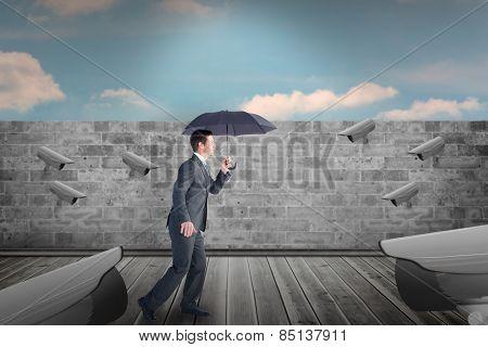 Businessman sheltering under black umbrella against blue sky over brick wall