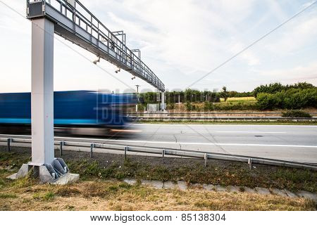 truck passing through a toll gate on a highway (motion blurred image; color toned image)