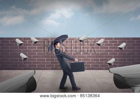 Businessman sheltering under black umbrella against blue sky over a brick wall