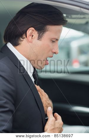 Businessman having a heart attack in his car