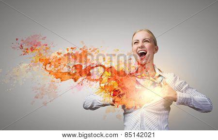 Attractive businesswoman opening her shirt like superhero