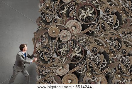 Young businessman making huge gears mechanism work