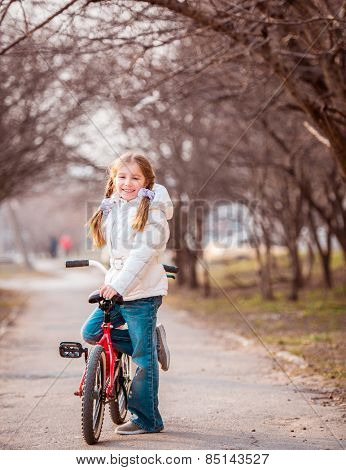 smiling happy little girl standing close to the bike in the spring