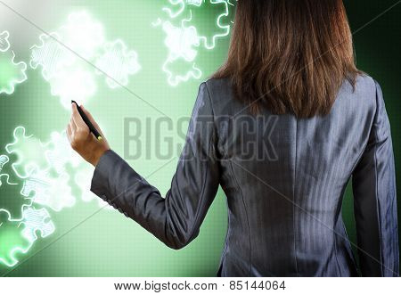 Rear view of businesswoman drawing puzzles with pen