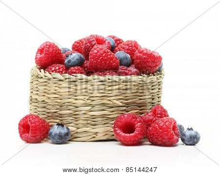 Raspberry and blueberry in basket isolated on white background