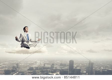 Young businessman sitting on cloud and meditating