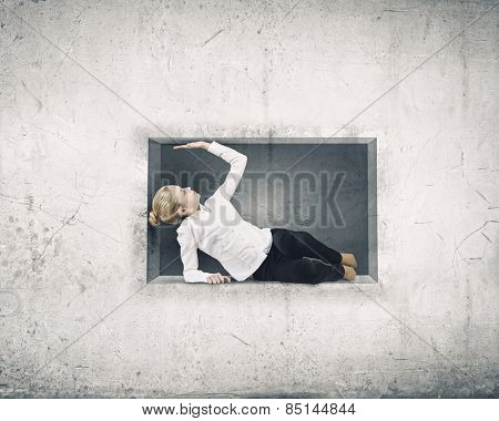 Young businesswoman trapped in stone cube in wall