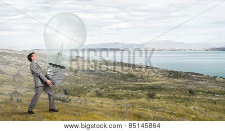 Businessman making effort to carry huge light bulb
