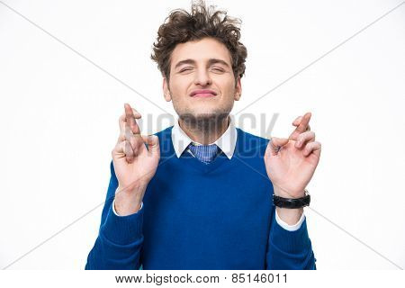 Young man with crossed fingers over white background