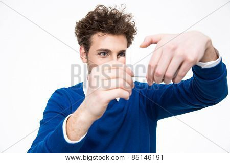 Hansome man making photo on smartphone over gray background