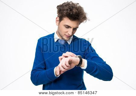 Handsome businessman looking at watch over white background