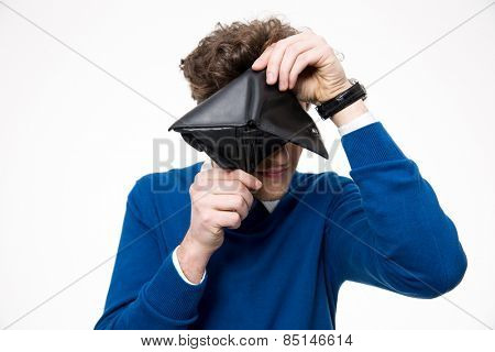 Young man looking through empty wallet at the camera