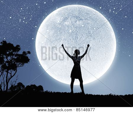 Silhouette of woman against full moon with hands up