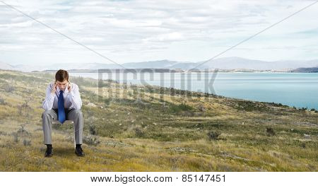 Troubled businessman sitting in chair on top of mountain